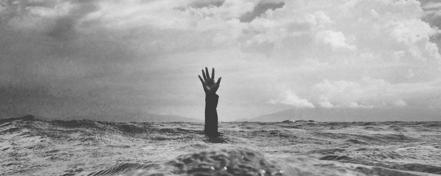 Mann streckt Hand aus Wasser-Bild zum Thema Suizid